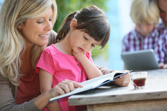 Mother and daughter reading book. Woman with daughter teaching how to read Royalty Free Stock Image