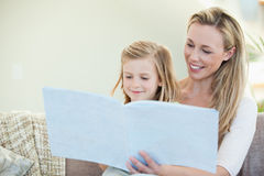 Mother and daughter reading on the couch Stock Images