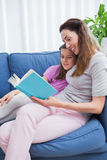 Mother and daughter reading on couch Royalty Free Stock Images