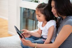 Mother and daughter reading electronic book. At home Stock Photos