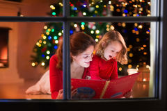 Mother and daughter reading at fire place on Christmas eve. Mother and daughter read a book at fireplace on eve. with celebrating Xmas. Decorated living room stock image