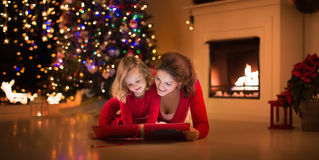 Mother and daughter reading at fire place on Christmas eve Royalty Free Stock Photography