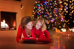 Mother and daughter reading at fire place on Christmas eve. Mother and daughter read a book at fireplace on Christmas eve. Family with child celebrating Xmas Stock Photography