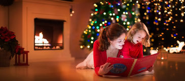Mother and daughter reading at fire place on Christmas eve. Mother and daughter read a book at fireplace on Christmas eve. Family with child celebrating Xmas Royalty Free Stock Image