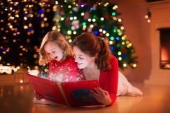 Mother and daughter reading at fire place on Christmas eve. Mother and daughter read a book at fireplace on Christmas eve. Family with child celebrating Xmas royalty free stock photo