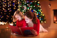 Mother and daughter reading at fire place on Christmas eve. Mother and daughter read a book at fireplace on Christmas eve. Family with child celebrating Xmas royalty free stock images