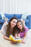 Mother and daughter reading on the floor Stock Images