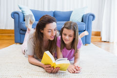 Mother and daughter reading on the floor Stock Image