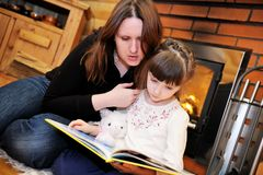 Mother and daughter reading in front of fireplace. Mother and daughter reading a book in front of fireplace Stock Images