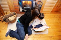 Mother and daughter reading in front of fireplace. Mother and daughter reading a book in front of fireplace, top view Royalty Free Stock Photos