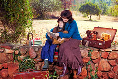 Mother and daughter reading in garden Stock Photo