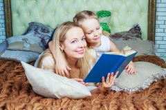 Mother and daughter reading. Happy young beautiful mother and daughter reading a book at home Royalty Free Stock Photo
