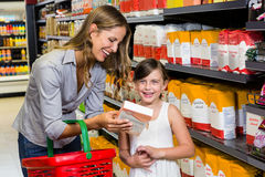 Mother and daughter reading ingredients on pack of flour Stock Image