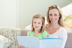 Mother and daughter reading a magazine on the sofa Stock Photos
