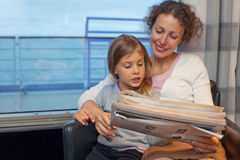 Mother daughter reading newspaper in ship Stock Photography