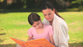 Mother and daughter reading outdoors Royalty Free Stock Images