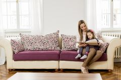 Mother and daughter reading in the room Royalty Free Stock Photos