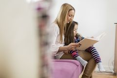 Mother and daughter reading in the room Stock Image
