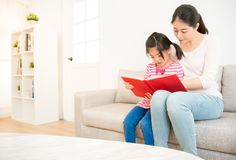 Mother and daughter reading story book. Beautiful mixed race asian mother accompany with her daughter reading story book together in the living room at home Royalty Free Stock Image