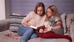 Mother and daughter reading story at home together stock video