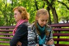 Mother and daughter before reconciliation. Mother and teen daughter sit on a park bench with their backs to each other in closed poses with slight smiles on stock photo