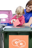 A mother and daughter recycling a cd Stock Images