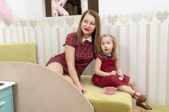 Mother and daughter in red dresses stock photo