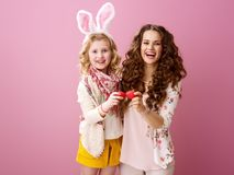 Mother and daughter red Easter eggs tapping isolated on pink Stock Image