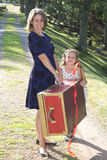 Packed and ready to go. Mother and daughter with a red suitcase are ready for an adventure Royalty Free Stock Image