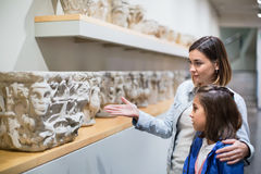 Mother and daughter regarding classical bas-reliefs. Smiling glad cheerful  mother and daughter regarding classical bas-reliefs in museum Royalty Free Stock Images