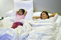Mother and daughter relax in bed enjoying a TV Show. stock photography