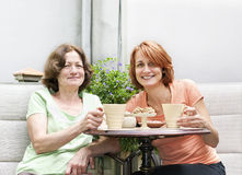 Mother and daughter relaxing in backyard Stock Images