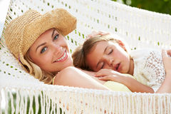 Mother And Daughter Relaxing In Beach Hammock Stock Images