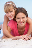 Mother And Daughter Relaxing On Beach Holiday. Smiling At Camera royalty free stock image