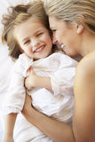 Mother And Daughter Relaxing In Bed Stock Photography