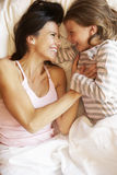 Mother And Daughter Relaxing In Bed Stock Images