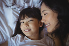 Mother and daughter relaxing on bed in bed room Royalty Free Stock Photos