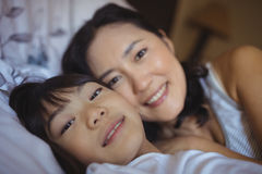 Mother and daughter relaxing on bed in bed room Stock Photo