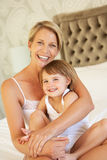 Mother And Daughter Relaxing In Bedroom Stock Photo