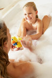 Mother And Daughter Relaxing In Bubble Filled Bath. Smiling Royalty Free Stock Photo