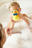 Mother And Daughter Relaxing In Bubble Filled Bath. Smiling Royalty Free Stock Image