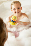 Mother And Daughter Relaxing In Bubble Filled Bath. Smiling Stock Photo