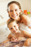 Mother And Daughter Relaxing In Bubble Filled Bath. Smiling To Camera Royalty Free Stock Photos