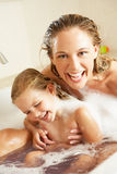 Mother And Daughter Relaxing In Bubble Filled Bath. Laughing Stock Photos