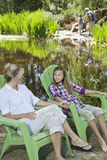 Mother and daughter relaxing on chairs with man and boy fishing in the background Royalty Free Stock Photos