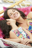 Mother And Daughter Relaxing In Garden Hammock Together Stock Images