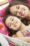Mother And Daughter Relaxing In Garden Hammock Together Royalty Free Stock Images
