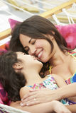 Mother And Daughter Relaxing In Garden Hammock Together royalty free stock image