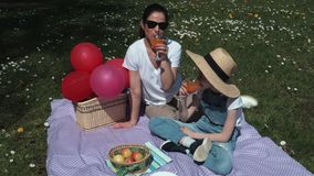Mother and daughter relaxing in picnic on meadow.Summer picnic concept stock footage