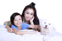 Mother and daughter relaxing with puppy on studio Royalty Free Stock Photos